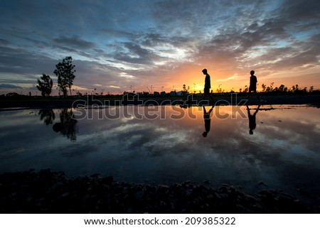 silhouette children and reflection sunset - stock photo