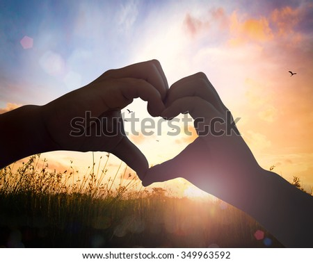 Silhouette children hands in the form of heart against the sky pass sun beams background. Hands in shape of love heart. Valentine's Day, Ecology, World Environment, Eco friendly, CSR, Cancer concept. - stock photo
