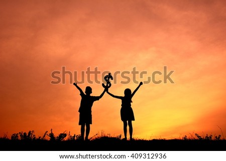 Silhouette children holding money in the sunset.