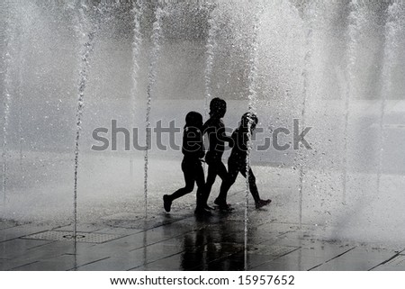 silhouette children playing in water fountains - stock photo