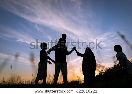 Silhouette children with parents playing on  sunset summer meadow