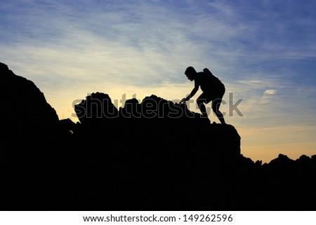 Silhouette Climbing a mountain  - stock photo