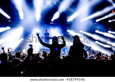 Silhouette Concert Person on Shoulders in Crowd at a Music Festival - Backlit with Lighting.