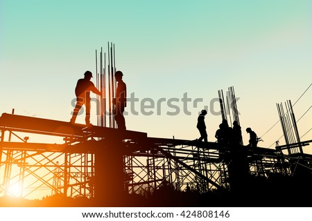 Silhouette construction industry engineer standing orders for construction team to work safely on high ground over blurred background sunset pastel for industry background. heavy industry concept. - stock photo