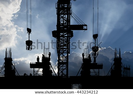 Silhouette Construction with workers with vibrant ray of light sky background - stock photo