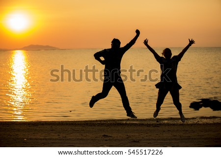 silhouette couple jumping on the beach