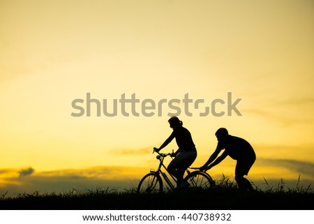 silhouette couple love teaching how to ride bicycle at beautiful sunset time.