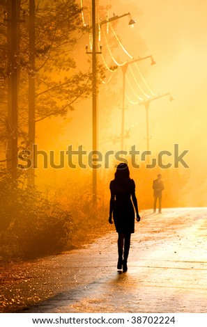 silhouette couple stand together in the sunlight - stock photo