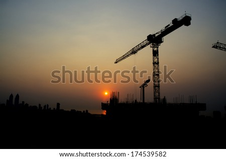 Silhouette crane on top of under construction building at sunset  - stock photo