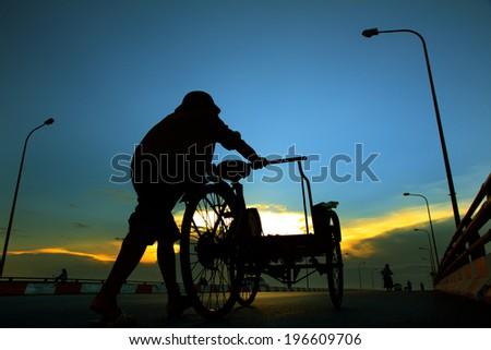 Silhouette cyclo in dawn light - stock photo