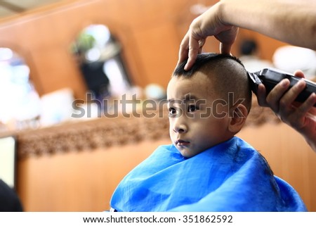 Silhouette edge  Asian cute boy trying to sit still for a barber THAILAND