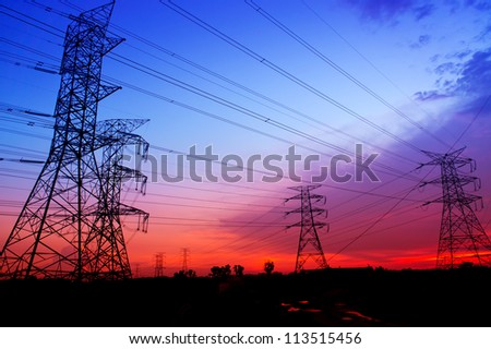 Silhouette electricity pylons during sunset - stock photo