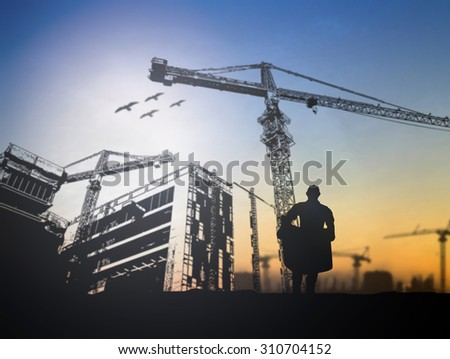 silhouette engineer  in a building site over Blurred construction site
