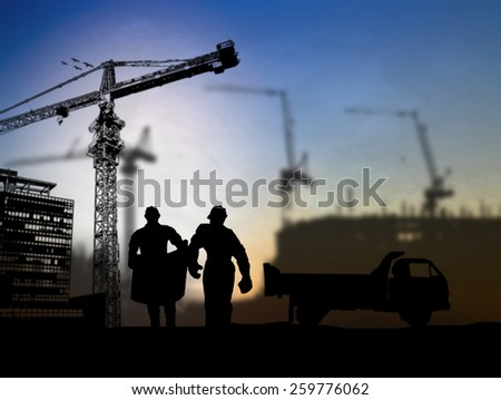 silhouette engineer looking at blueprints in a building site over Blurred construction  - stock photo