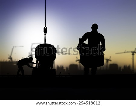 silhouette engineer looking at blueprints in a building site over Blurred construction worker  - stock photo
