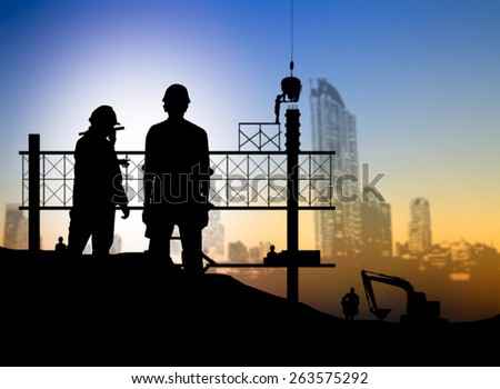 silhouette engineer looking blueprint in a building site over Blurred construction worker on construction site - stock photo