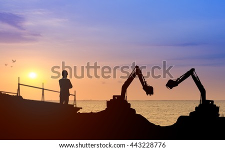 Silhouette engineer looking construction worker nearly sea beach with sunset background in a building site.Over Blurred construction worker on construction site nearly sea beach with sunset background - stock photo