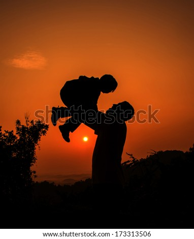 Silhouette father and son playing at the mountain during sunrise - stock photo