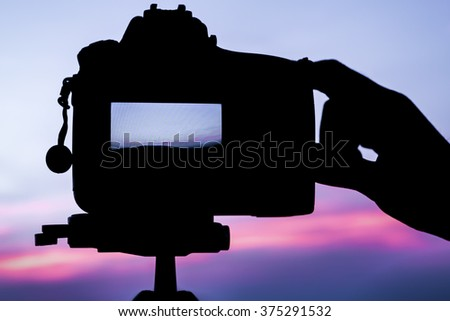 Silhouette Filter : Photographer's Hand and DSLR camera focus on sunrise lanscape sceen - stock photo