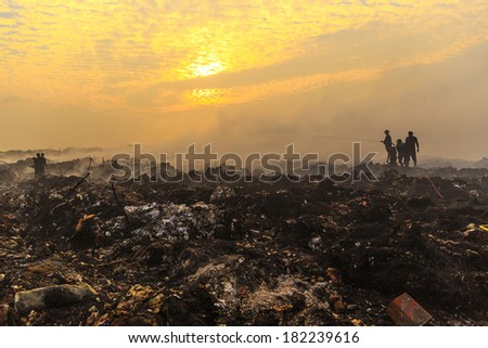 Silhouette Firefighters extinguishing a fire wearing smoke mask at landfill garbage large area at sunset - stock photo