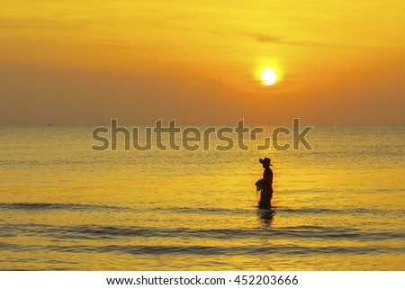 silhouette fisherman working at beach on sunrise time,select focus with shallow depth of field.