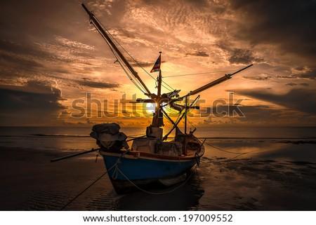silhouette fishing boat on sea. - stock photo