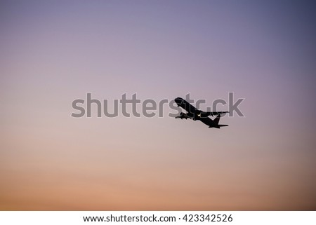 Silhouette fllying plane while dawn with purple and red background in wide angle