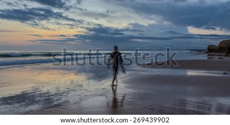 Silhouette form surfer on the background seascape at sunset. Portugal. - stock photo