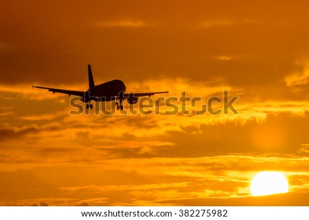 Silhouette from a landing plane that is flying to the airport. Photo taken during a nice colorful sunrise.