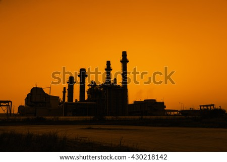 Silhouette gas turbine electrical power plant at dusk - stock photo
