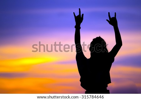 Silhouette girl show hands love sign at sunset