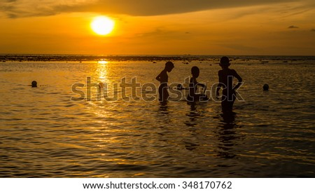 Silhouette group of kids playing at the beach in sunset time