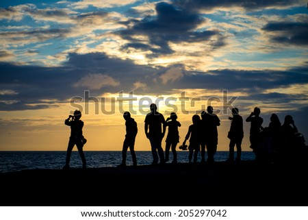 Silhouette group of people watching sunset at the coast sunset at the coast - stock photo
