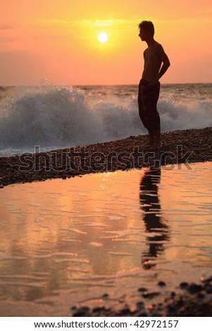 Silhouette guy on sunset wavy beach - stock photo