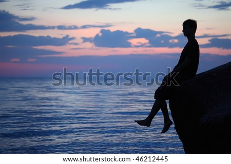 Silhouette guy sitting on breakwater in evening near sea - stock photo