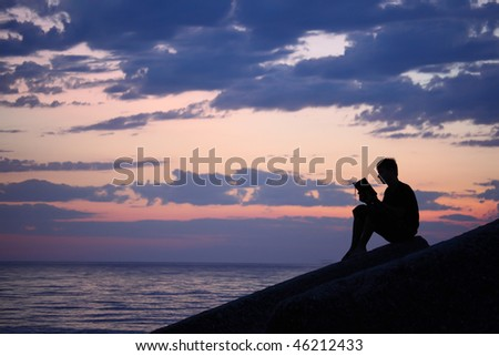 Silhouette guy sitting on breakwater in evening near sea, reads book - stock photo