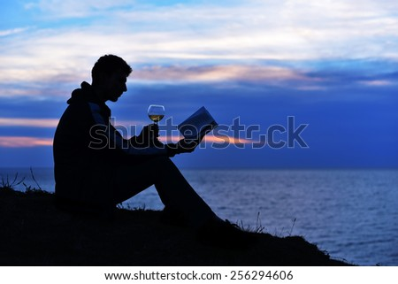 Silhouette guy sitting on breakwater in evening near sea, reads book with glass of wine. Silhouette of man reading in the sunset light, sea, ocean, nature, wine - stock photo