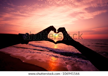 Silhouette hand in heart shape with sunrise in the middle and beach background - stock photo