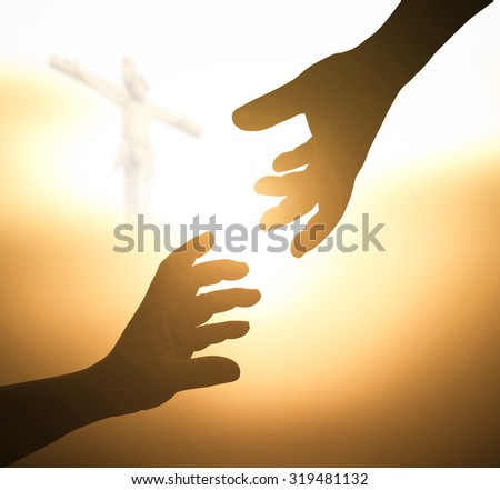 Silhouette hand of a man reaching to hand of GOD over blurred Jesus on the cross over sunset background. - stock photo