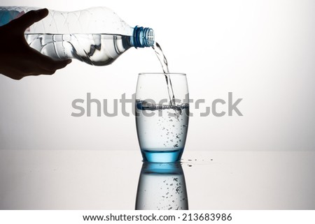 Silhouette Hand Pouring Water In Water Glass - stock photo