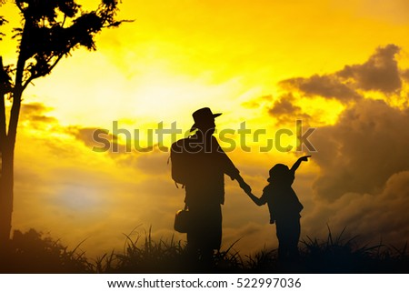 Silhouette happy family.Father and little daughter silhouettes play at sunset