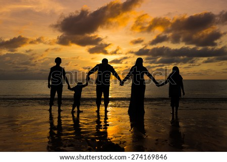 Silhouette Happy family holding hand during sunset at the beach - stock photo