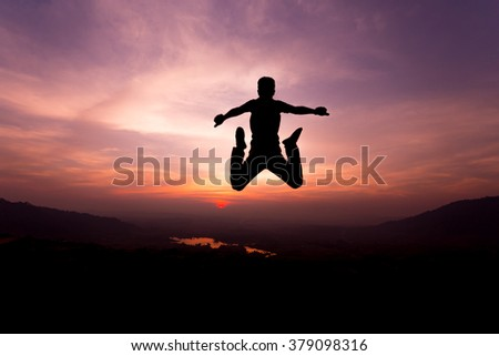 silhouette happy man jumping for joy on the peak of the mountain, cliff at sunset.The positive reaction of human.Success, winner, happiness concept
