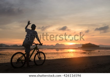 Silhouette, happy man riding bicycle feeling motivated on the beach in the morning with sunrise sky background.