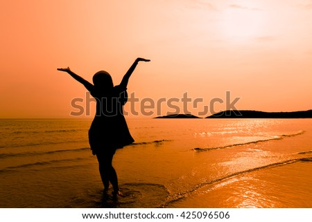 Silhouette happy woman walking on beach,Happy young woman walking with arms stretched out standing on a beach. Happy young woman feeling relax and walk on the beach. Happy woman relaxing at sea - stock photo