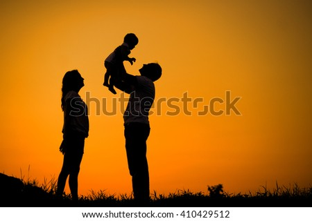 Silhouette happy young family on sunset background - stock photo