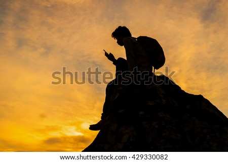 silhouette  hiker sitting on a cliff edge enjoying scenic view and send picture message to a friend check in on location on social media