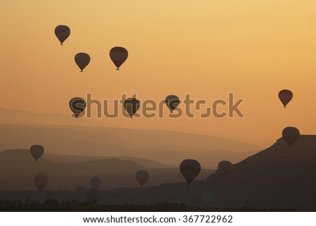 Silhouette Hot Air Balloons flying during Sunrise over Cappadocia - stock photo
