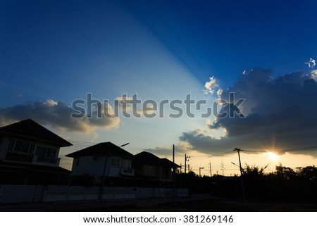 silhouette house of village suburb with beautiful sun light on clear blue sky background - stock photo