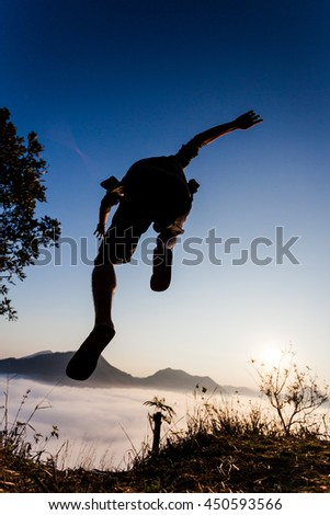 Silhouette human jump in the air on mountain summit with beautiful morning light and clear blue sky.